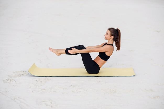 Młoda piękna kobieta praktykujących jogę, robienie ćwiczeń push up na plaży nad morzem. joga fitness i koncepcja zdrowego stylu życia. piękna kobieta w sportach jest ubranym robić ćwiczeniu na joga macie.