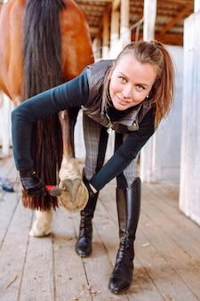 Młoda piękna kobieta przed jazdą czyści kopyta konia specjalną szczotką