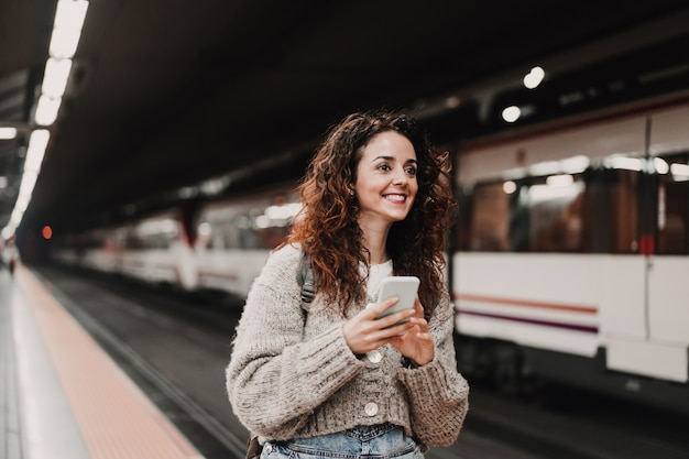 Młoda piękna kobieta przy dworcem używa telefon komórkowego przed łapać pociąg. widok z tyłu. podróż, technologia