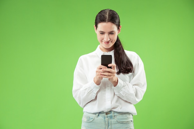 Młoda piękna kobieta przy użyciu telefonu komórkowego na kolor zielony ścianie. koncepcja ludzkich emocji twarzy.