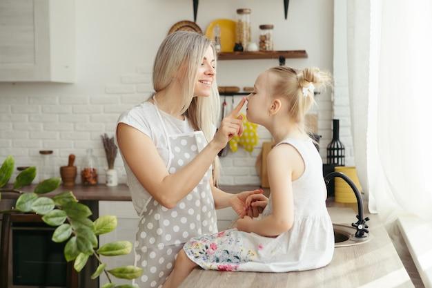 Młoda piękna kobieta przytula i całuje swoją śliczną córeczkę. tonowanie.