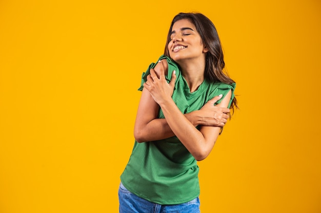 Młoda piękna kobieta przytulanie się szczęśliwa i pozytywna, uśmiechnięta pewna siebie. miłość do siebie i troska o siebie