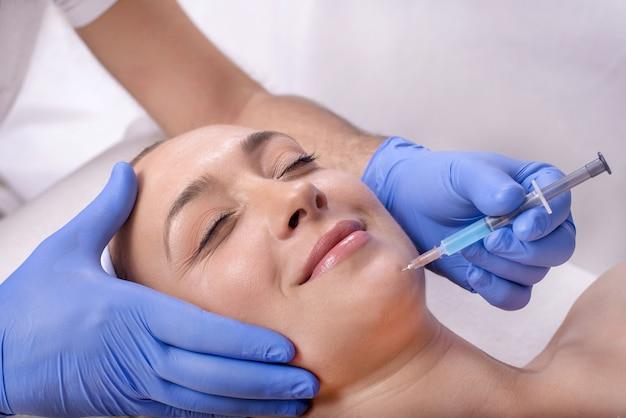 Młoda piękna kobieta rasy kaukaskiej podczas leczenia kwasem hialuronowym w gabinecie kosmetycznym