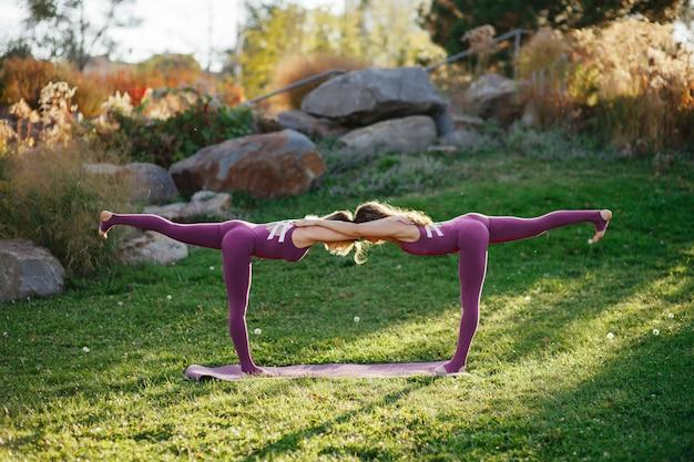 Młoda piękna kobieta robi ćwiczenia jogi na trawie na łące. dziewczyna ćwiczy kobry asanę plenerową z zamkniętymi oczami. spokój i relaks, kobiece szczęście.