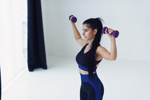 Młoda piękna kobieta robi ćwiczenia z hantlami w studio fitness