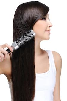 Młoda piękna kobieta robi jej długie proste zdrowe włosy