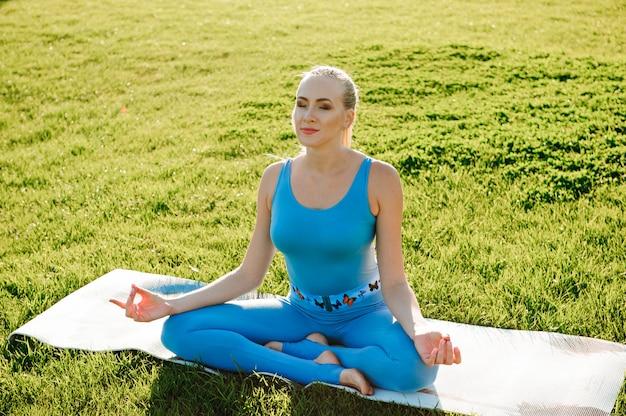 Młoda piękna kobieta robi joga ćwiczeniom w parku