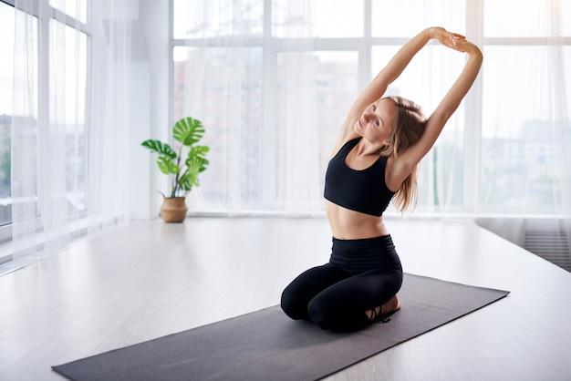 Młoda piękna kobieta robi joga w nowoczesnym jasnym pokoju z dużymi oknami. koncepcja jogi w domu.
