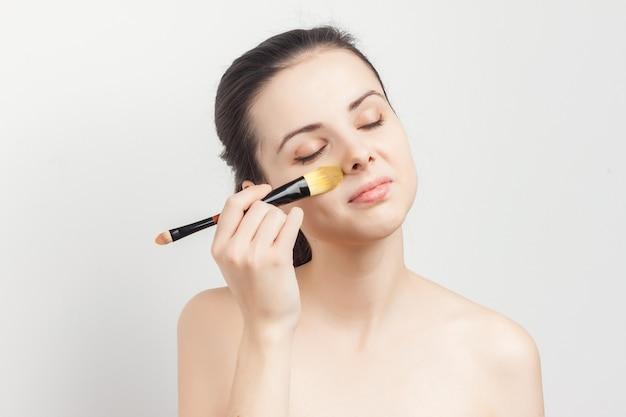 Młoda piękna kobieta robi makijaż
