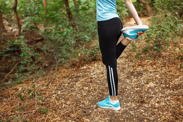 Młoda piękna kobieta robi nogi rozciąganiu przed biegać