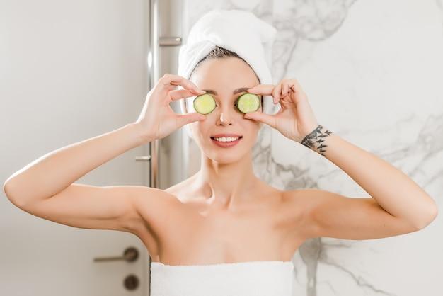 Młoda piękna kobieta robi ogórkowej masce zawijającej w ręcznikach w łazience