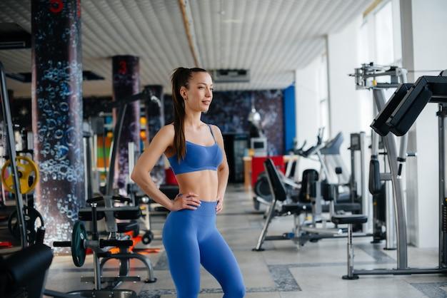 Młoda piękna kobieta robi sport na siłowni w masce podczas pandemii.