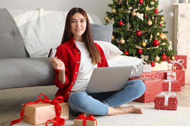 Młoda piękna kobieta robi zakupy na boże narodzenie w świątecznym wnętrzu w domu