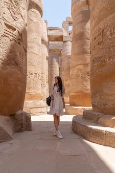 Młoda piękna kobieta robi zdjęcia między kolumnami sali hipostylu świątyni karnaka w luksorze, egipt.