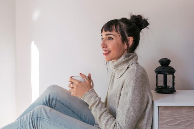 Młoda piękna kobieta siedzi na białym kocu i trzyma filiżankę kawy. relaks w domu. wewnątrz