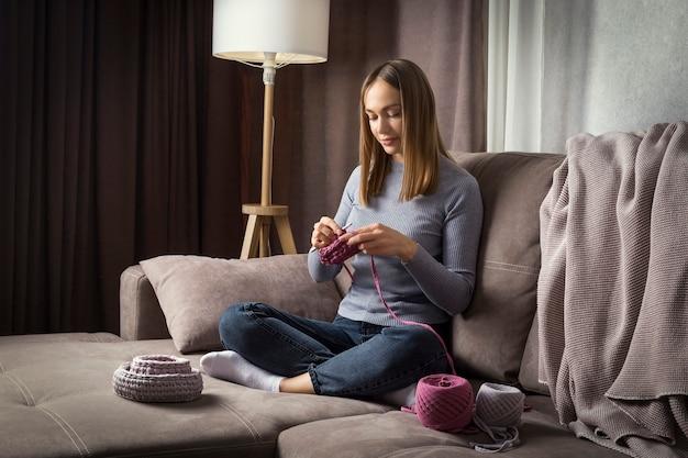 Młoda piękna kobieta siedzi na kanapie i robi na drutach w domu