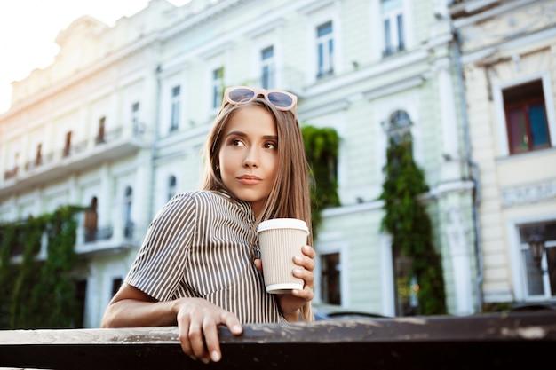 Młoda piękna kobieta siedzi na ławce, trzymając kawę