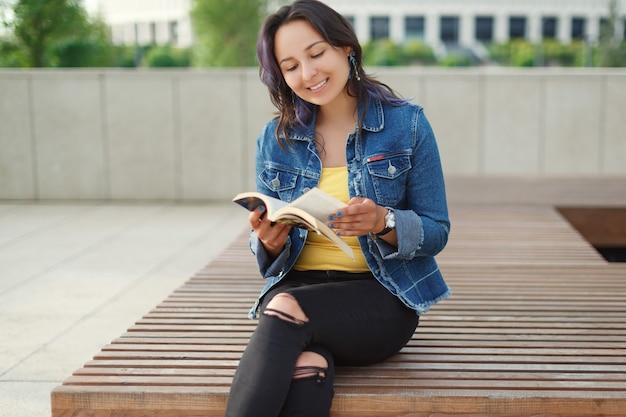 Młoda piękna kobieta siedzi na ławce w parku