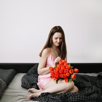 Młoda piękna kobieta siedzi na łóżku i trzyma bukiet czerwonych tulipanów