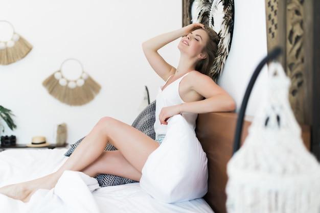Młoda piękna kobieta siedzi na łóżku w domu