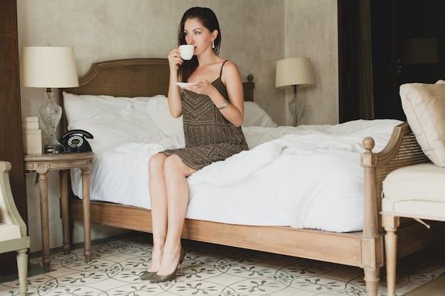 Młoda piękna kobieta siedzi na łóżku w hotelu, stylowa sukienka, zmysłowy nastrój, picie kawy, trzymając kubek