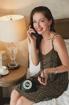 Młoda piękna kobieta siedzi na łóżku w hotelu, stylowa suknia wieczorowa, zmysłowy nastrój, rozmawia przez telefon, uśmiechnięta, zalotna, szuka, seksowna