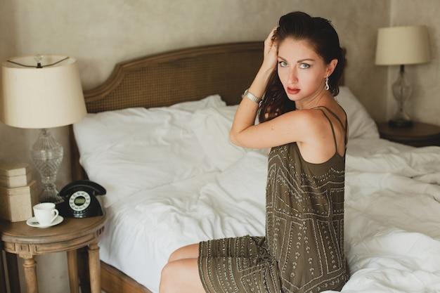 Młoda piękna kobieta siedzi na łóżku w pokoju hotelowym, stylowa suknia wieczorowa, zalotny, seksowny, modny strój, białe prześcieradła
