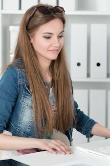 Młoda piękna kobieta siedzi na swoim miejscu pracy w biurze.