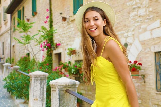 Młoda piękna kobieta siedzi na ulicy starego włoskiego miasta w toskanii