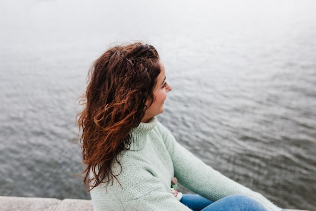 Młoda piękna kobieta siedzi nad rzeką o zachodzie słońca, podziwiając widoki na porto. koncepcja podróży