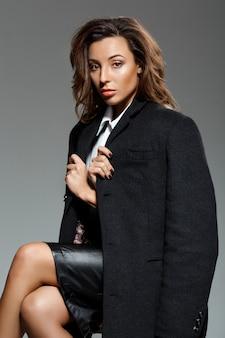 Młoda piękna kobieta siedzi nad szarości ścianą