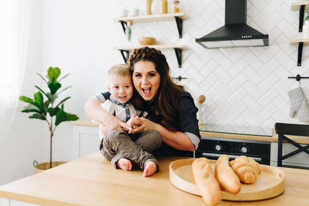 Młoda piękna kobieta siedzi przy stole w kuchni rano z małym dzieckiem
