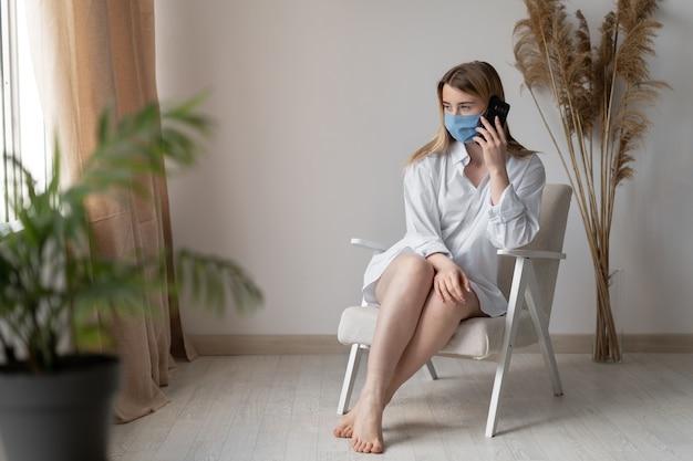 Młoda piękna kobieta siedzi w domu podczas choroby. przyjmuje zamówienia telefonicznie. noszona jest osłona twarzy. praca zdalna.