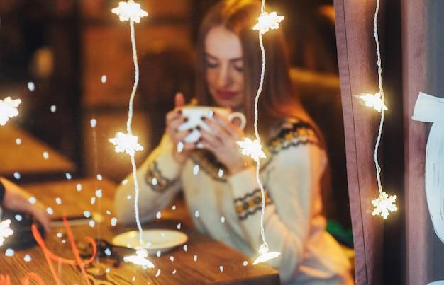 Młoda piękna kobieta siedzi w kawiarni, picia kawy. boże narodzenie, nowy rok, walentynki, ferie zimowe