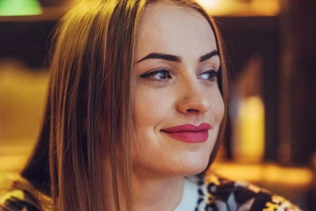 Młoda piękna kobieta siedzi w kawiarni, picia kawy. model patrząc w górę. boże narodzenie, nowy rok, walentynki, ferie zimowe