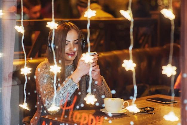 Młoda piękna kobieta siedzi w kawiarni, picia kawy. model słuchania muzyki. boże narodzenie, nowy rok, walentynki, ferie zimowe