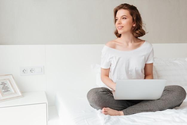 Młoda piękna kobieta siedzi w pomieszczeniu za pomocą laptopa