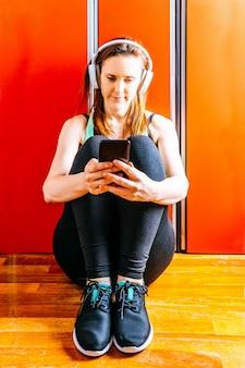 Młoda piękna kobieta siedzi w siłowni szatni ze słuchawkami muzycznymi na czacie na smartfonie.