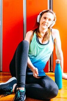 Młoda piękna kobieta siedzi w szatni siłowni ze słuchawkami muzycznymi, trzymając smartfon