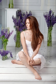Młoda piękna kobieta siedzi wśród bukietów kwiatów. przemyślane spojrzenie na bok. koncepcja pielęgnacji skóry. piękna kobieta z naturalnym makijażem