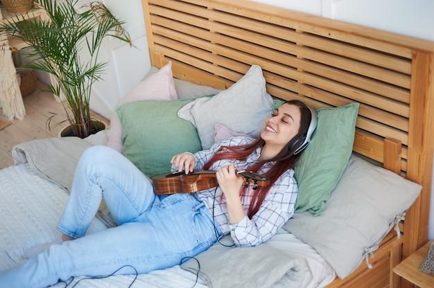 Młoda piękna kobieta, słuchając muzyki w słuchawkach, grając na ukulele, leżąc na łóżku.