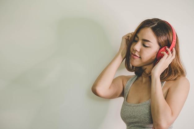 Młoda piękna kobieta słuchania muzyki ze słuchawkami