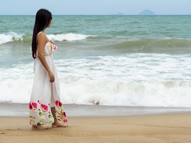 Młoda piękna kobieta spaceru aline brzegiem morza i patrząc na morze. czas letni, podróże, turystyka, relaks lub koncepcja wakacji
