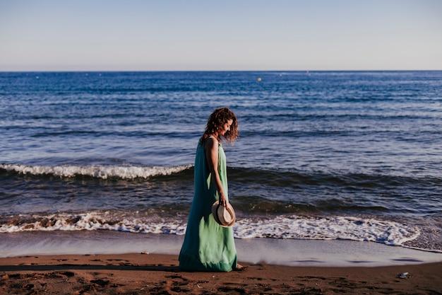 Młoda piękna kobieta spaceru na plaży o zachodzie słońca