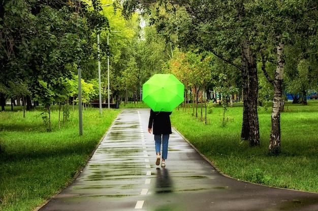 Młoda piękna kobieta spaceru pod zielonym parasolem