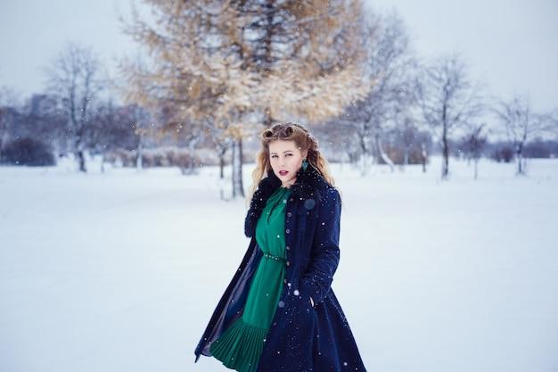 Młoda piękna kobieta spaceru w parku i oddychanie świeżym zimowym powietrzem i cudowne uczucie. model plus rozmiar