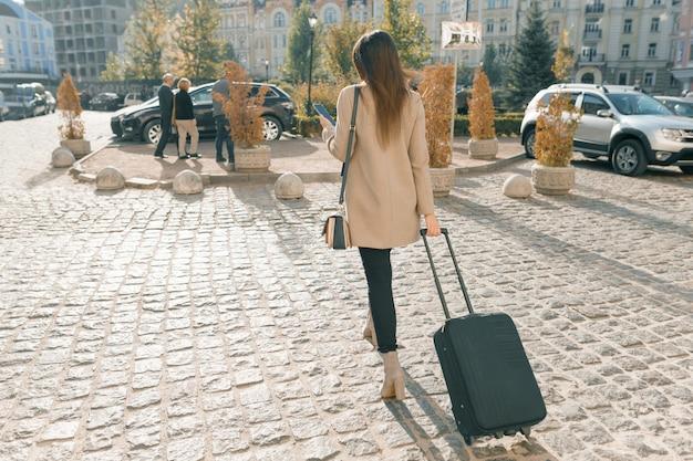 Młoda piękna kobieta spaceru wzdłuż ulicy miasta z walizką podróży