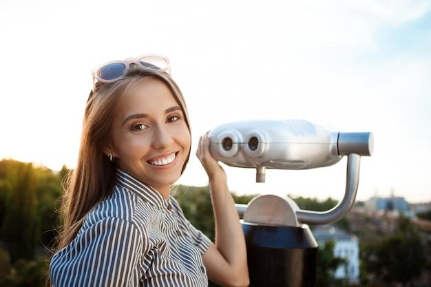 Młoda piękna kobieta spacerując po mieście, pozowanie w pobliżu lornetki, uśmiechając się.
