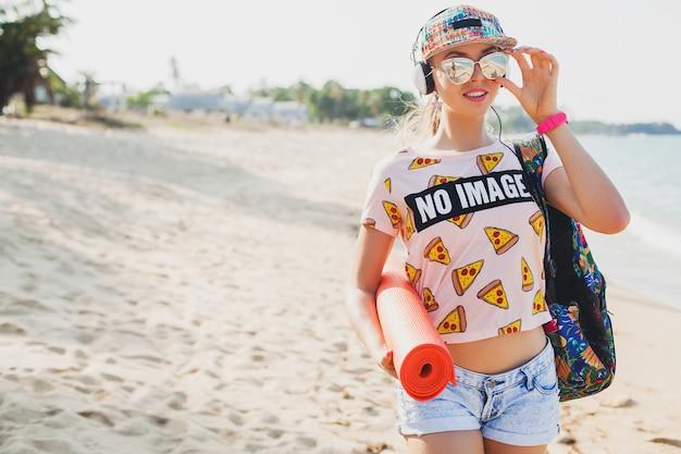 Młoda piękna kobieta spacerująca po plaży z matą do jogi, słuchanie muzyki na słuchawkach, styl hipster sport swag, spodenki dżinsowe, t-shirt, plecak, czapka, okulary przeciwsłoneczne, słoneczny, letni weekend, wesoły