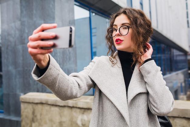 Młoda Piękna Kobieta Spacerująca Ulicą Miasta W Szarym Płaszczu, Moda Jesień, Okulary, Trzymając Smartfon, Robienie Zdjęć Selfie, Uśmiechnięta, Szczęśliwa Darmowe Zdjęcia